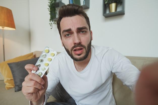 집에서 모바일 장치 앞에서 온라인 상담 중에 의사에게 독감, 감기 또는 covid19로 물집을 보여주는 수염 난 남자