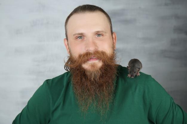 Бородатый мужчина с забавной крысой на цветной поверхности