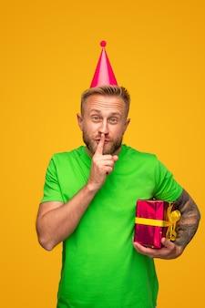 Бородатый мужчина с подарочной коробкой показывает секретный жест