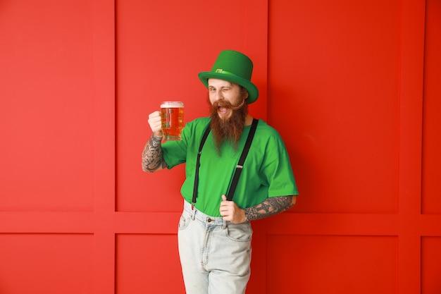 色の壁にビールのガラスを持つひげを生やした男。聖パトリックの日のお祝い
