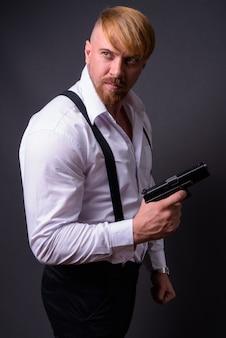 Бородатый мужчина с пистолетом на сером