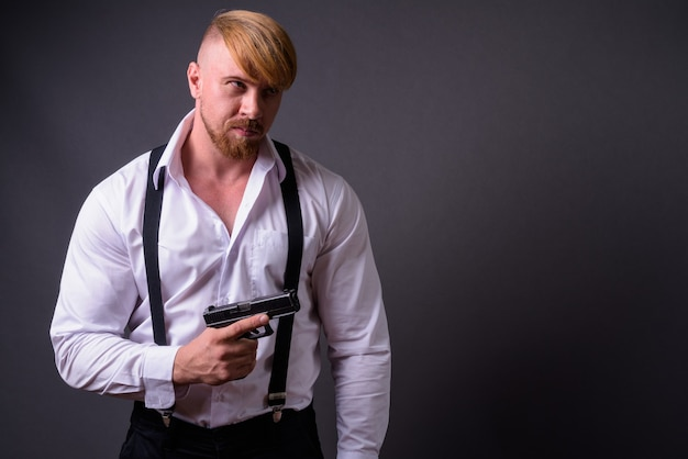 Бородатый мужчина с пистолетом на сером Premium Фотографии