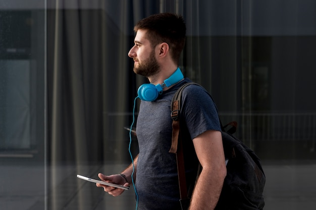 Bearded man with headphones holding smartphone