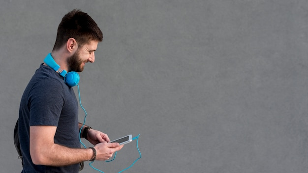 Bearded man with headphones on neck using tablet