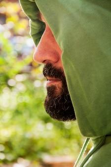 Bearded man with hood. portrait of mid aged man with beard and green sweatshirt