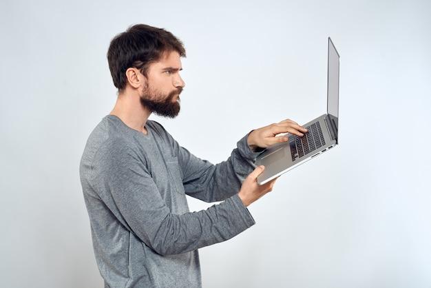 明るい背景の手にラップトップを持つひげを生やした男