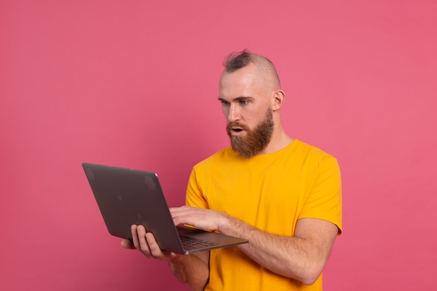 Bearded man with laptop isolated shock emotions on pink background
