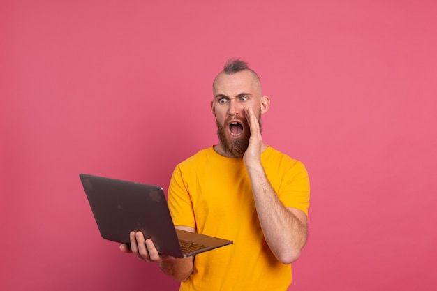 Bearded man with laptop isolated shock emotions screaming on pink background