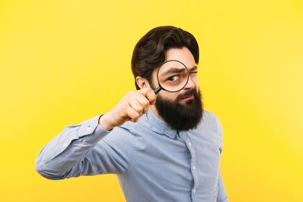 Бородатый мужчина с лупой на желтом фоне