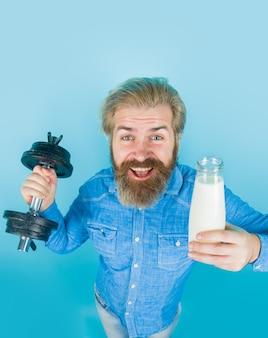 ミルクダンベルのひげを生やした男。健康的な生活様式。乳糖。筋肉のためのビタミン。カルシウム。乳製品。