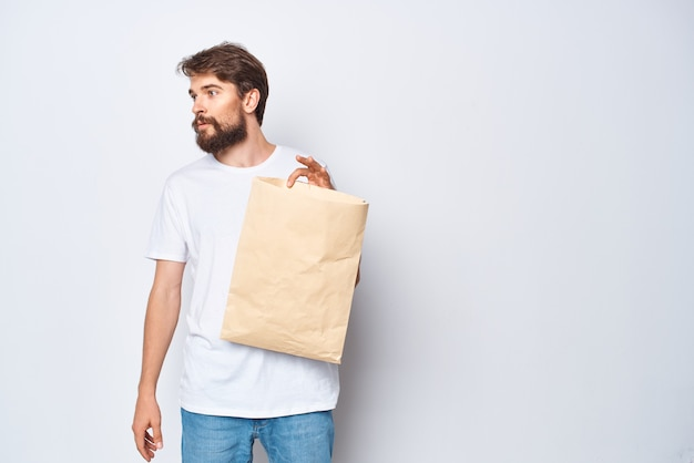 Бородатый мужчина с бумажным пакетом в макете магазина белой футболки