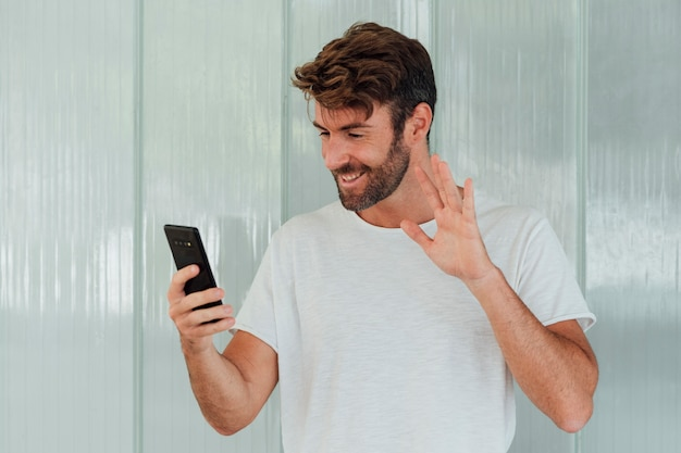 Bearded man with phone waiving at camera