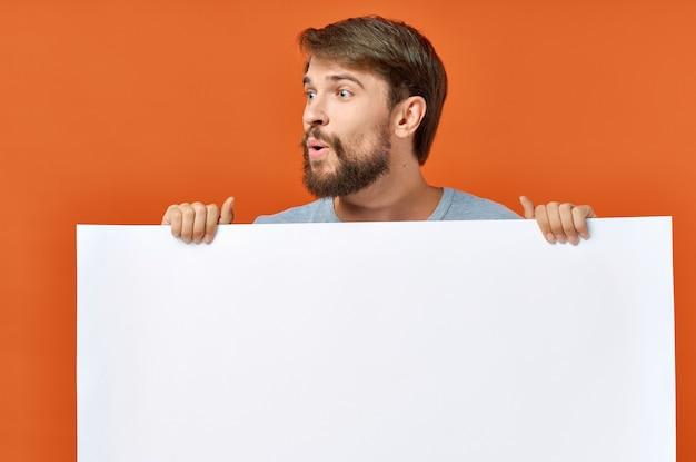 Бородатый мужчина с плакатом в руке на оранжевом фоне копией пространства.