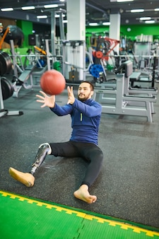 Bearded man with prosthetic leg catching ball