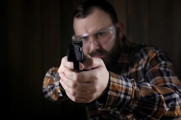 권총 사격 시 보호용 고글과 귀 훈련을 한 수염 난 남자