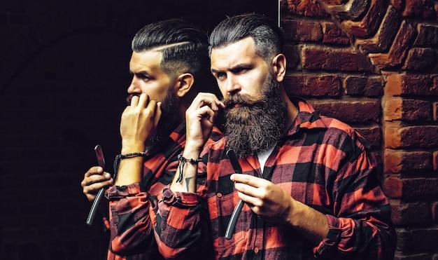 거울 근처 면도칼으로 수염 된 남자
