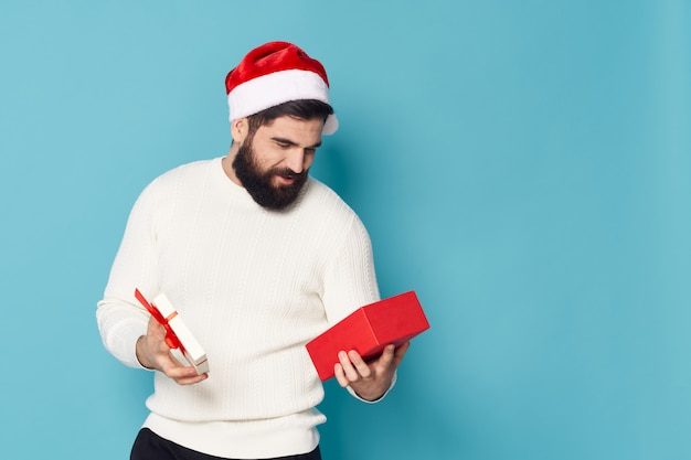 Bearded man with santa hat holding a gift
