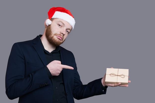 공식적인 마모를 입고 산타 모자와 수염 난 남자는 여유 공간 근처의 회색 벽에 포즈를 취하는 그의 손에 현재를 가리키고 있습니다.