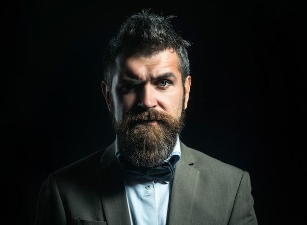 蝶ネクタイと高級スーツで真面目な顔のひげを生やした男。