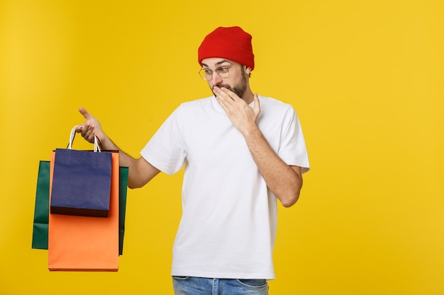 黄色に分離された幸せな気持ちで買い物袋を持つひげを生やした男。