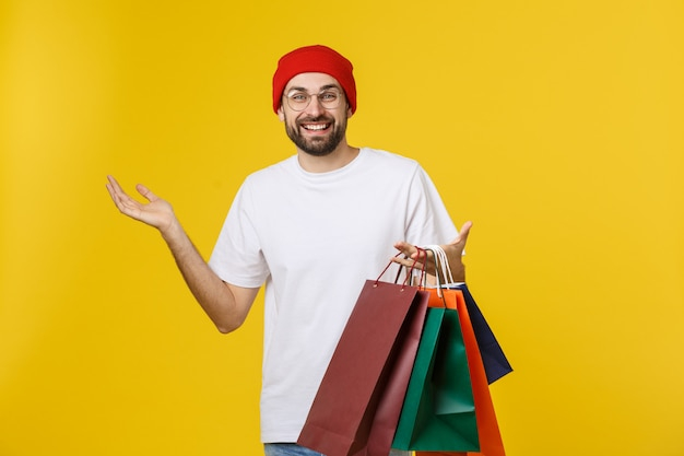 Bearded man with shopping bags with happy feeling isolated