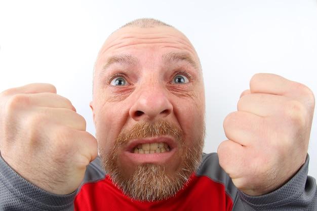 Бородатый мужчина с сильными эмоциями и со сжатыми кулаками крупным планом на белом