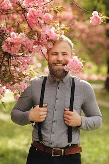 Bearded man with stylish haircut with sakura flowers. hipster in in suspenders near with branch of sakura flowers in teeth. harmony with nature concept.