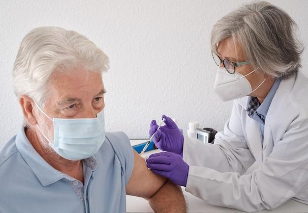 외과용 마스크를 쓴 수염 난 남자가 여성 의사로부터 백신 접종을 받고 있습니다. 코로나바이러스 예방 접종 개념