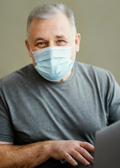 Uomo barbuto con mascherina chirurgica che tiene laptop