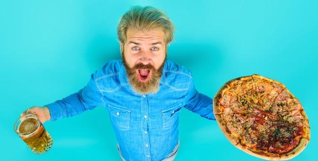 レストランでおいしいピザとビールのガラスを持つひげを生やした男。おいしいファーストフードの食事。イタリア料理。ランチまたはディナー。