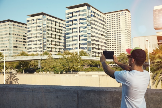 Bearded man with tattoos taking a photo of city buildings and trees