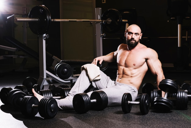 Bearded man with towel amidst dumbbells