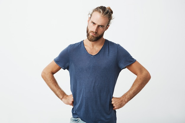 Bearded man with trendy haircut holding hands on waist