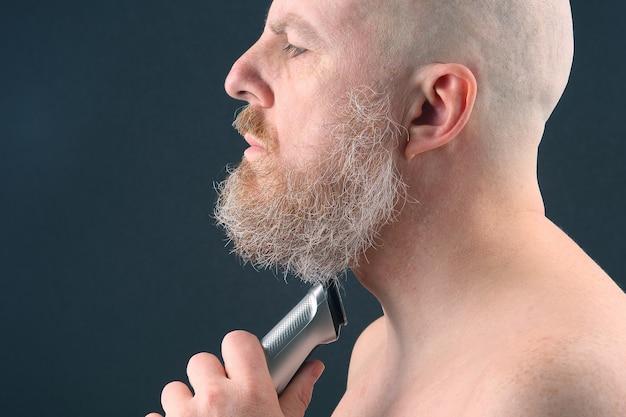 손에 수염을 조정하는 트리머와 수염 된 남자