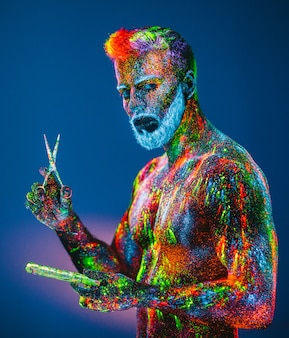 Bearded man with ultraviolet powder in a barbershop