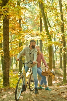 Bearded man and woman relaxing in autumn forest. romantic couple on date. date and love. autumn date hike in forest. romantic date with bicycle. couple in love ride bicycle together in forest park.