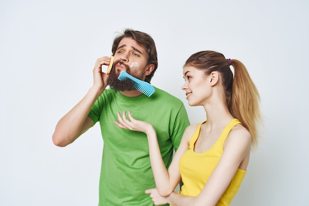 Bearded man next to woman shaving facial in bathroom