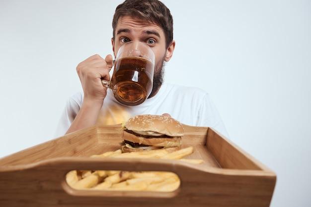 Бородатый мужчина деревянный поднос с фаст-фудом пивом весело фри гамбургеры