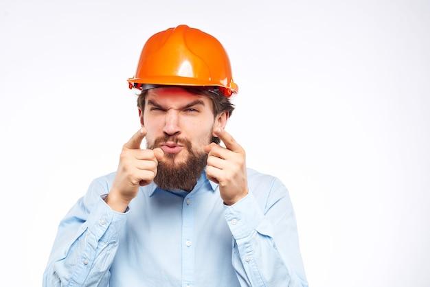 あごひげを生やした男は建設業界の保護服で働いています。高品質の写真