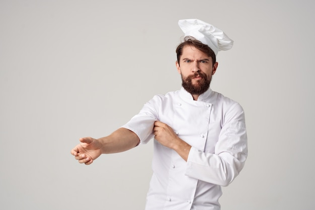 あごひげを生やした男は制服の職業キッチンの明るい背景を動作します。高品質の写真