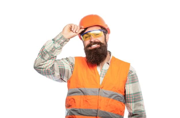 헬멧이나 단단한 모자를 쓰고 있는 수염이 난 남자 노동자. 남자 건축업자, 산업. 안경 만들기. 웃는 작성기의 초상화입니다. 헬멧에 단단한 모자, 감독 또는 수리공을 쓴 빌더