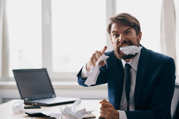 オフィスでラップトップのために働いているひげを生やした男感情不満の専門家