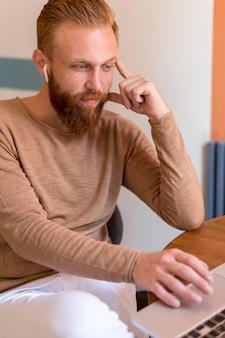Uomo barbuto che lavora alla sua scrivania