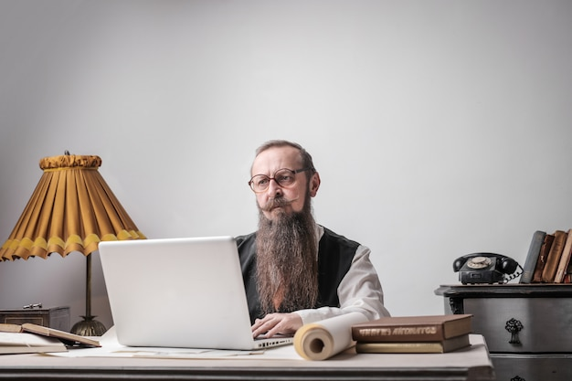 Bearded man working on a laptop