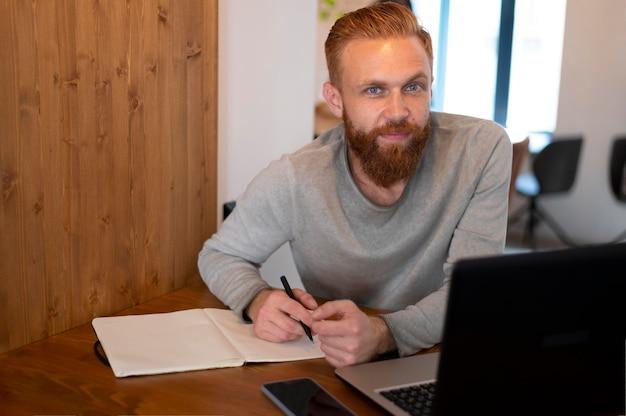 Бородатый мужчина работает на своем ноутбуке