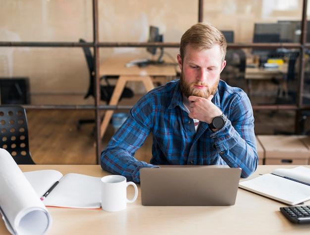 Бородатый мужчина работает на ноутбуке на рабочем месте