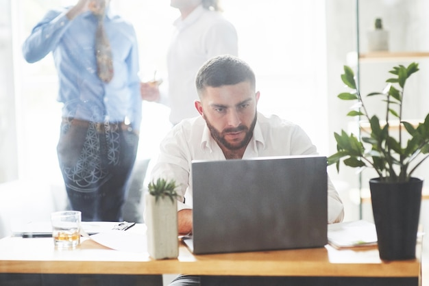 Bearded man working with laptop in office room with two employees behind