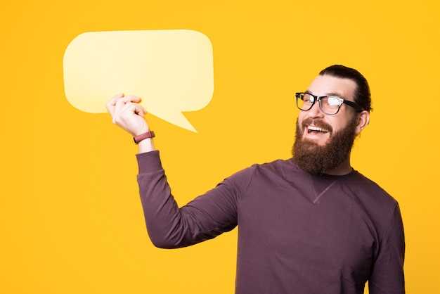 Bearded man woth glasses is holding a speech bubble and looking away is smiling