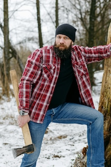 Bearded maniac with an ax walking on a snowy road