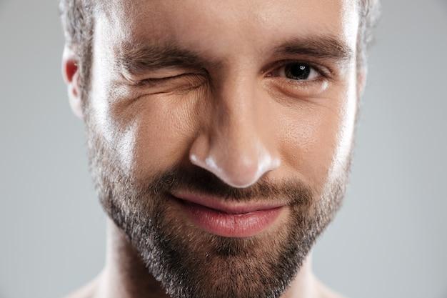 La faccia da uomo barbuto fa l'occhiolino